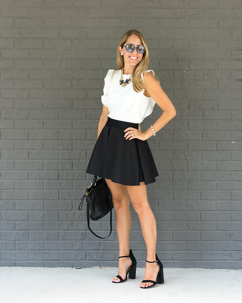 White ruffle top, black skater skirt, statement necklace