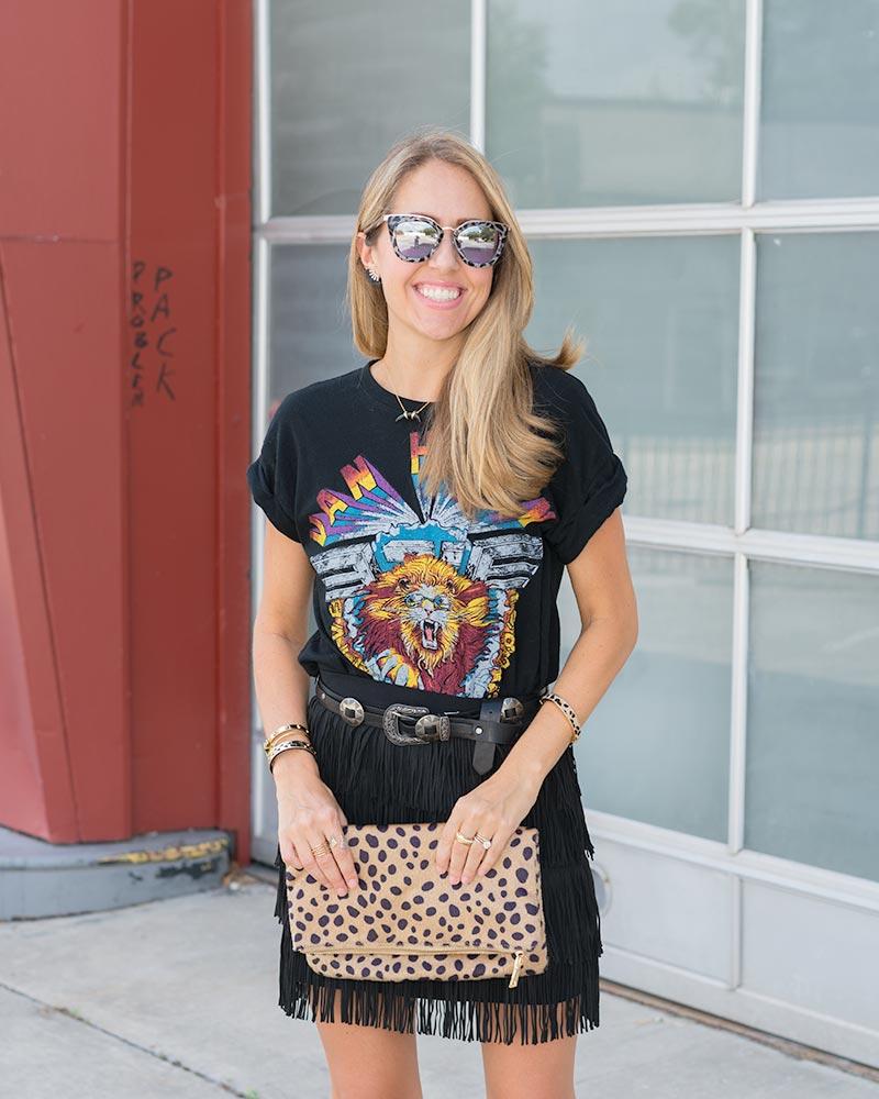 Black graphic tee, fringe skirt, leopard clutch