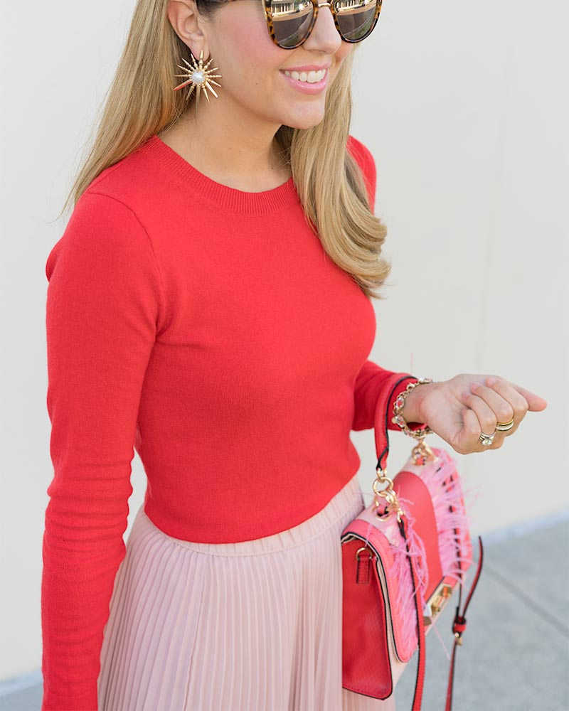 Red sweater, pink pleated skirt