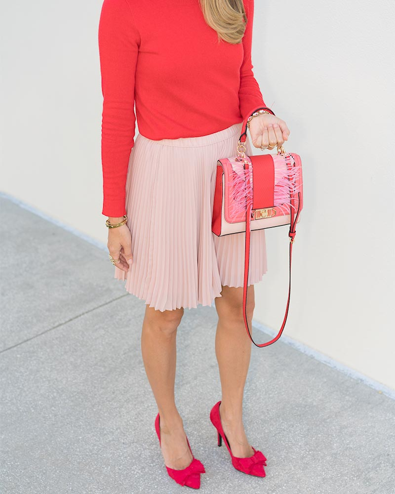 Red sweater, pink pleated skirt, bow pumps