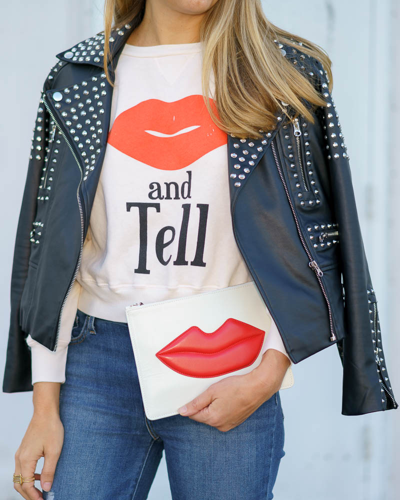 Studded leather jacket, graphic sweatshirt, lips clutch