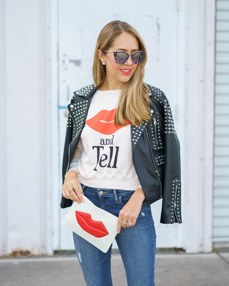 Studded leather jacket, graphic sweatshirt, lips clutch