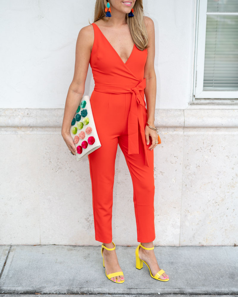 Orange red jumpsuit, pom pom clutch, yellow shoes