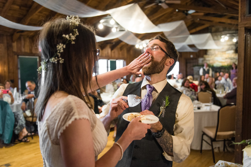 bride smashing cake in the groom's mouth