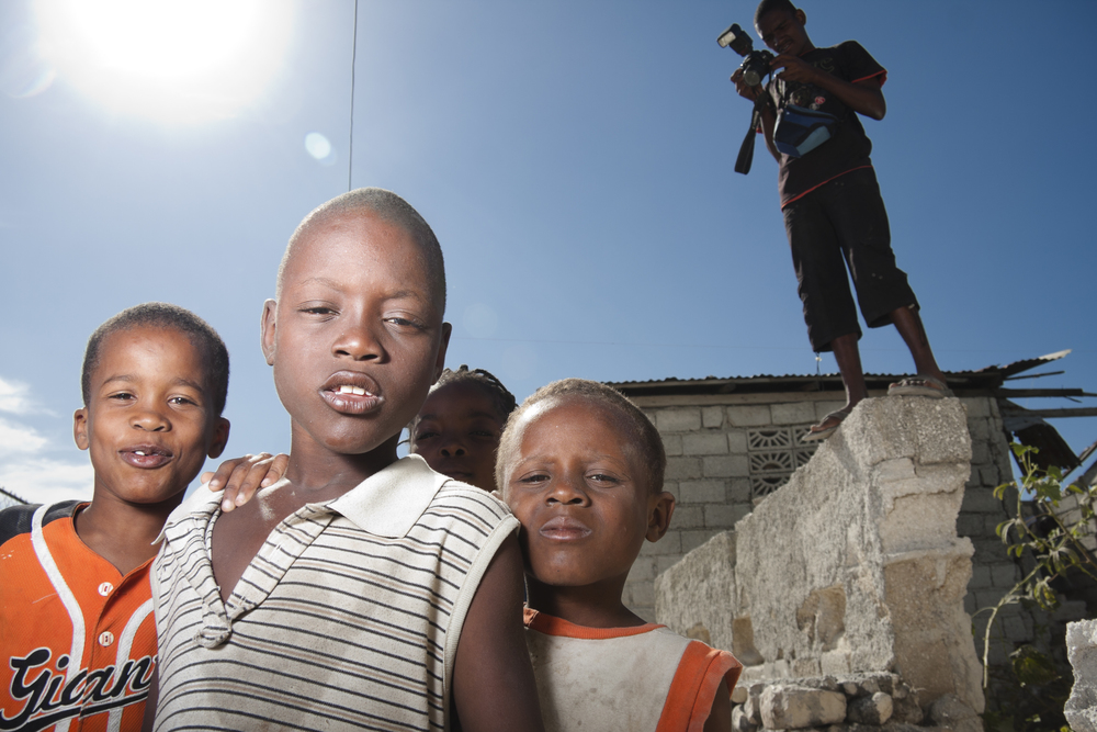 Port-au-Prince. 22 December 2011. Children posing for a photograph, while Fortuné is checking the settings on his camera.