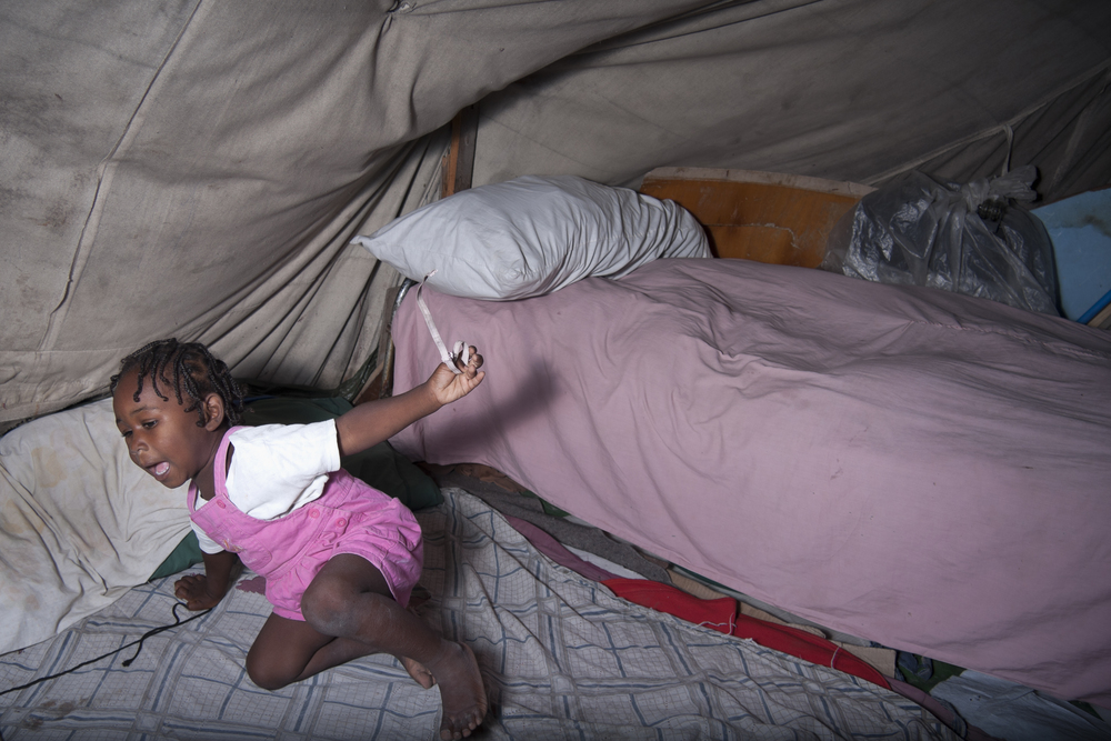 Port-au-Prince. 18 December 2011. Fortune's half sister playing inside the family's tent, using a bra strap as a toy.