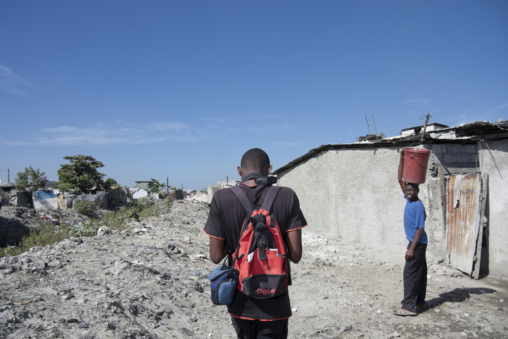 Port-au-Prince. 22 December 2011. Fortuné walking into Village de Dieu with a camera around his neck.