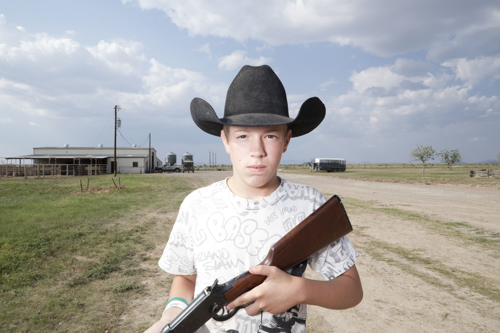 USA. Texas. Marfa. August 2013. 12-year-old Clayton Kibbe posing with his rifle.