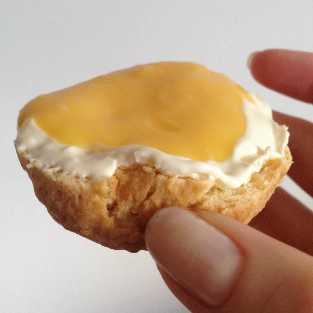 Passievruchten curd op een scone met clotted cream