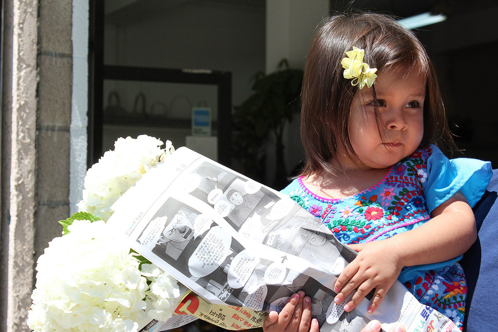 My daughter dressed like a Mexican while holding fresh flowers wrapped in a Japanese newspaper circa 2011.