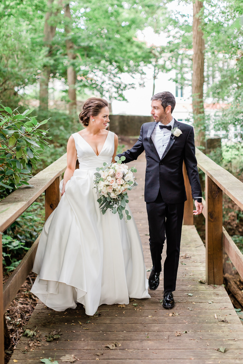 Couple walking the wooden bridge at Tupper Manor