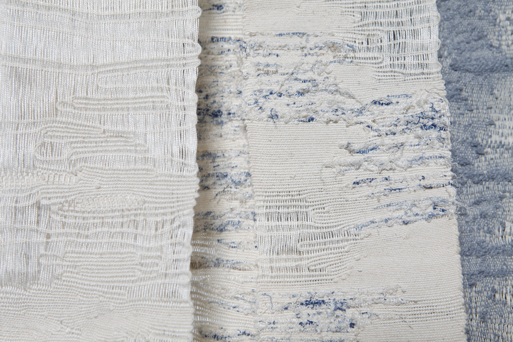 Woven pieces made using yarn and fibre produced by de-constructing old fabrics.  Cotton twill fabric was taken apart by hand to produce ivory coloured yarn and ivory and blue fibre.  A warp was made on a table loom from old crochet cotton and strips were woven by hand, inspiration for their texture came from worn and threadbare fabrics.  Katherine Taylor, 2015