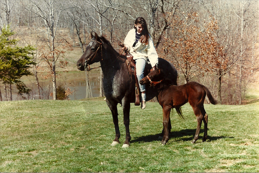 Dana riding her horse with colt at side