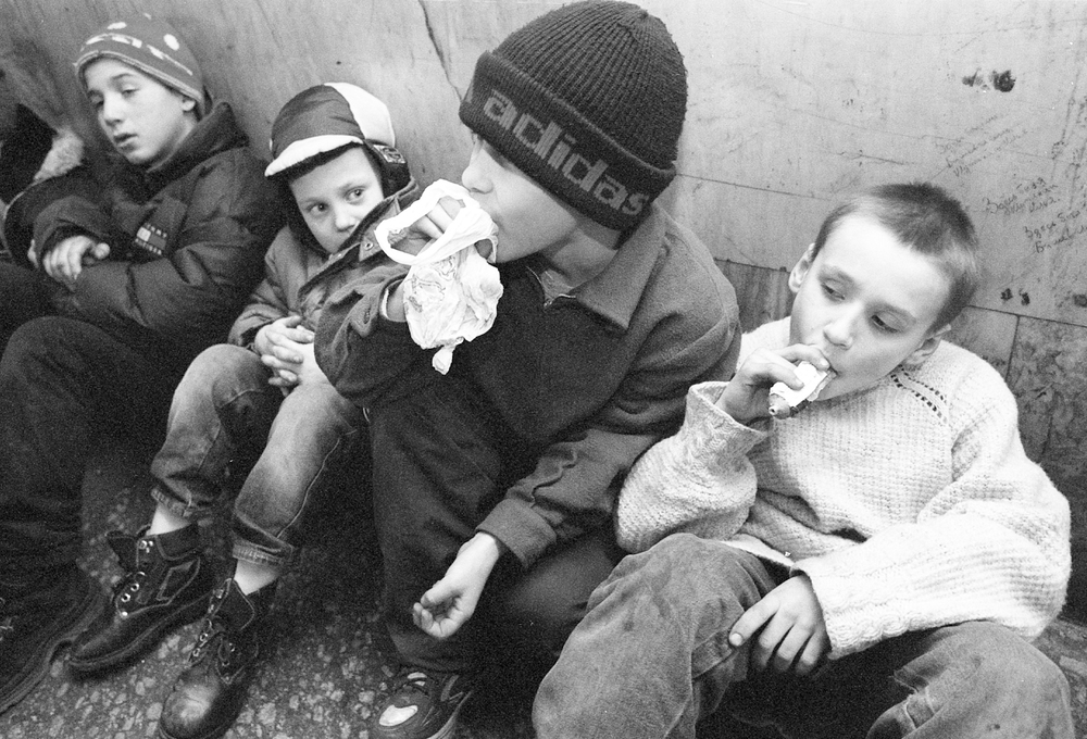 Moscow, Russia. Kursky train station .Kiril Glagolov, 10, (center)  inhaling glue inside the train station. He and the other kids are  homeless and addicted to glue.