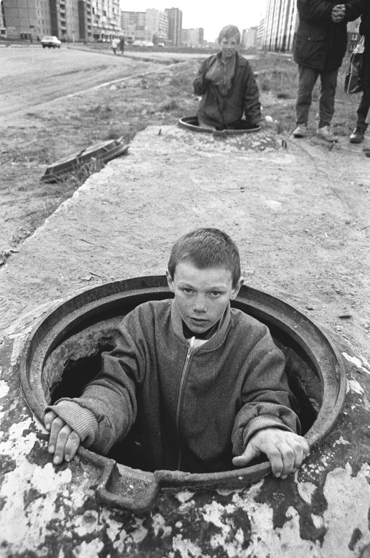 St. Petersburg, Russia A homeless boy climbing out of his underground hiding place. He and  other homeless kids sleep on top of the hot water pipes under the street  on the outskirts of the city. Almost all the kids are addicted to  sniffing glue. Published in Washington Post.