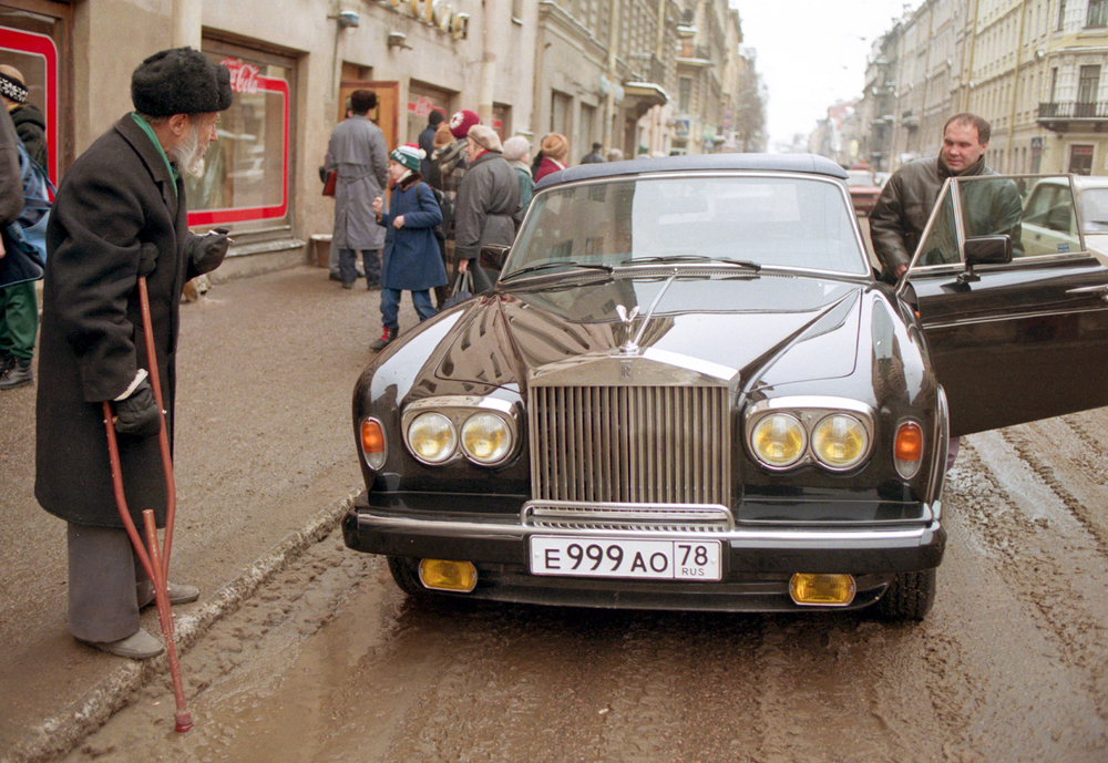 An elderly man watches a wealthy Russian step into his Rolls Royce in downtown St. Petersburg, Russia.