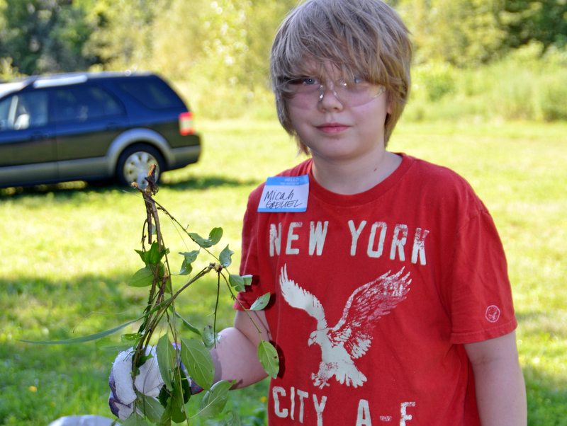 Micah Greuel with buckthorn he removed.
