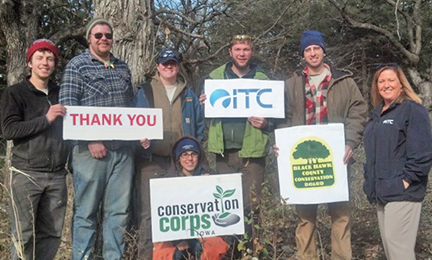 Iowa corps members thank ITC for funding restoration work at Cedar Bend Savanna near Cedar Falls, Iowa. Standing, from the left are: Andrew Montgomery, Scott Cressler, Allison McIntosh, Ian Wolf and Josh Bruecken.  On the right: Angela Jordan, ITC area manager, and in the front: Tracey Prenger, crew leader.
