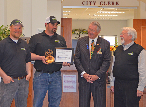 Zach Dieterman, field coordinator, Dustin Looman, assistant manager, both from the Southern District, and at far right, Len Price, executive director, accepted the award from Mayor Brede.