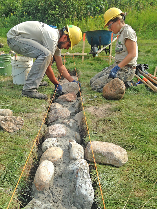 Jacob Roman and Taryn Orona constructed the stone foundation for the log shelter at Coffee Pot Landing.