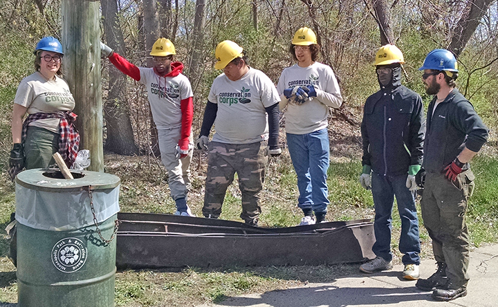 The Minneapolis North Commons crew posed by a huge piece of metal debris they retrieved from the banks of the Mississippi.