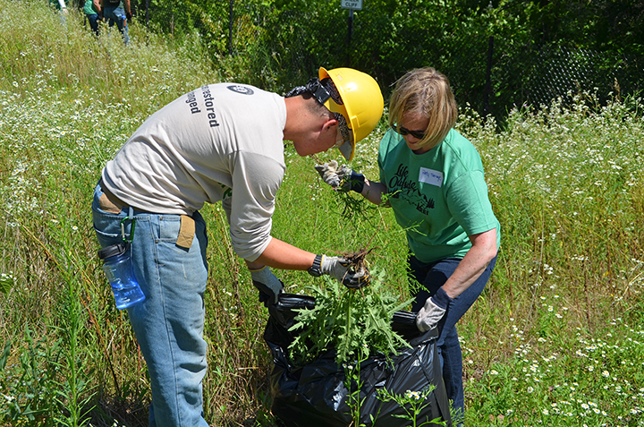 Summer Youth Corps crew member Mason Anderson and Andersen Corporation employee Patti Savage bagged invasive plants removed from the Boom Site.