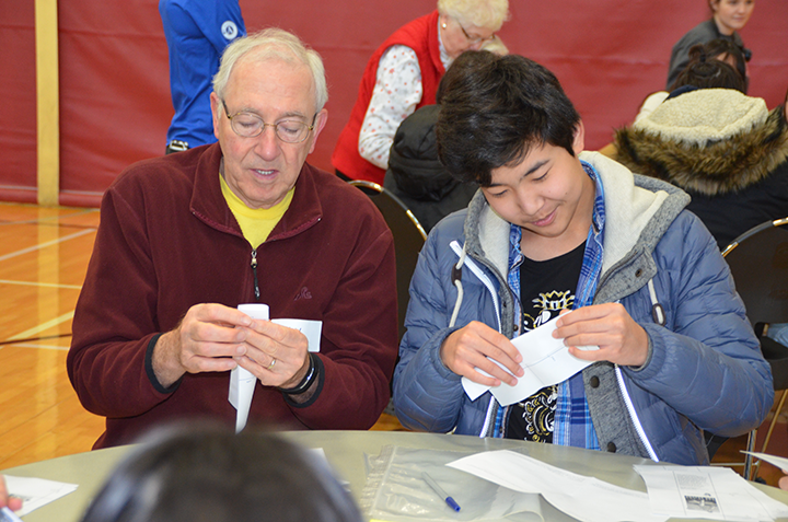 A YMCA senior and St. Paul Prep School student shared stories as they packaged prairie grass seed.