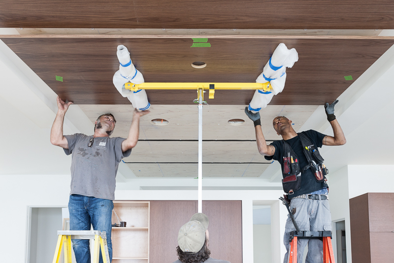 Simul-snapping: carpenters snap floating walnut panels to the ceiling in the dining room.