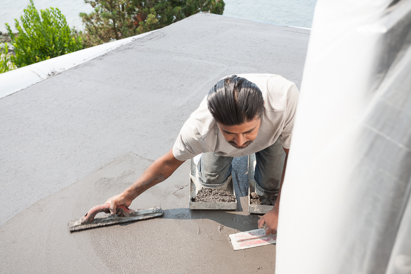 Concrete skills: we self perform much of our architectural concrete. Here, concrete foreman Rene Cruz Garcia trowels out the freshly poured concrete on the second floor deck.