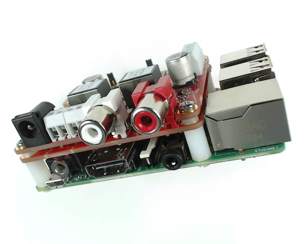 a JustBoom digital audio player controlled by a  raspberry pi 3B (green) with DAC HAT and and amp pcbs stacked on top (red.) a very small, feature rich, versatile, and highly connective player device with an astoundingly low cost.