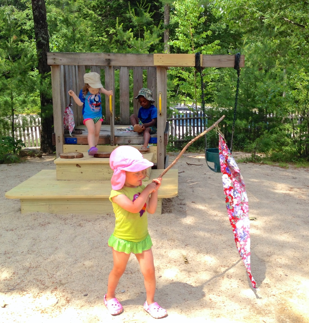 Toddlers parade around and help decorate their play yard with flags for our Summer Solstice Festival