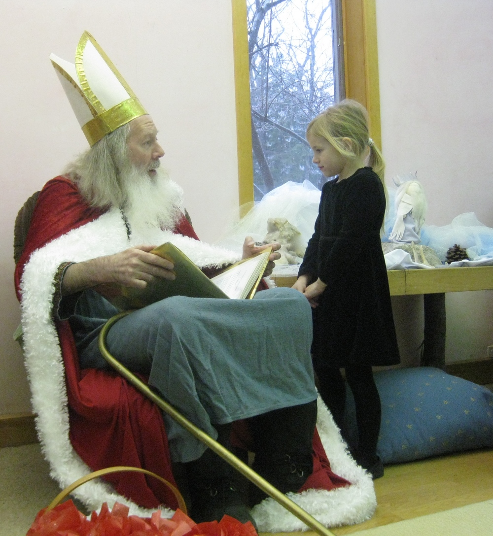 St. Nicholas reading about a child's good deeds in his golden book
