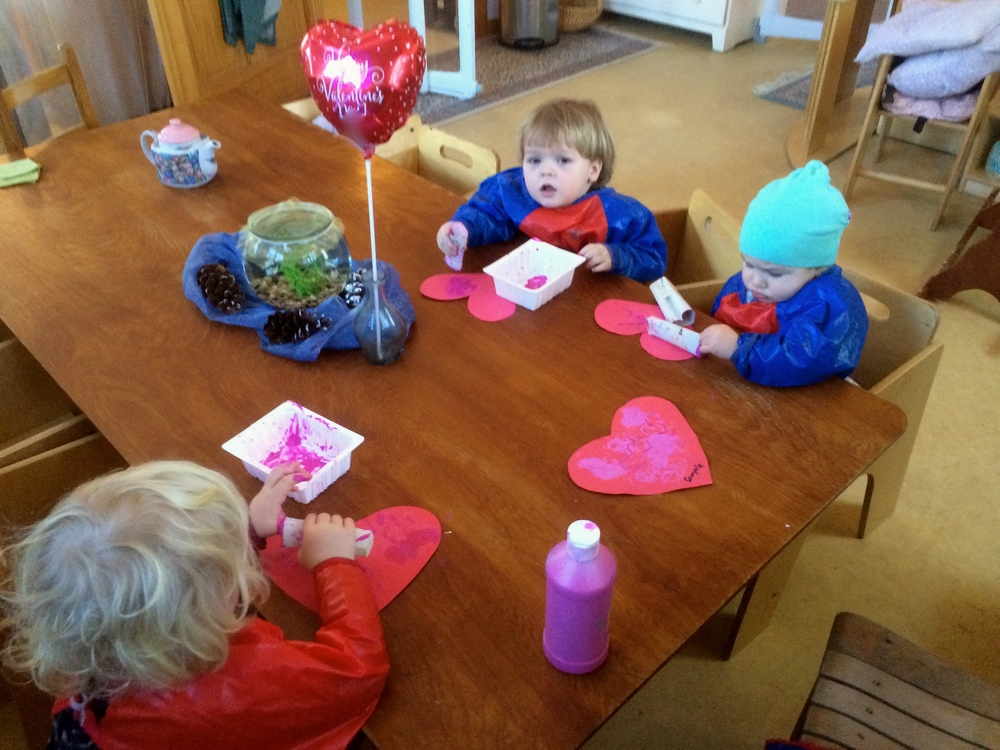 Toddlers stamp painting valentines for their grandparents