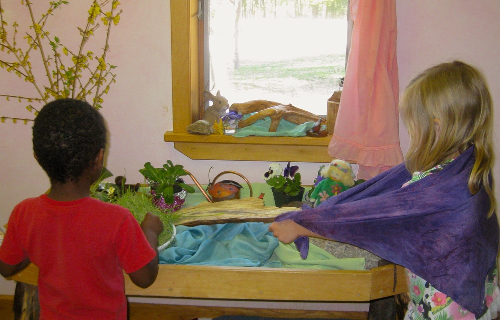 Children looking at Lady Spring puppet and Easter grass growing on the preschool nature table
