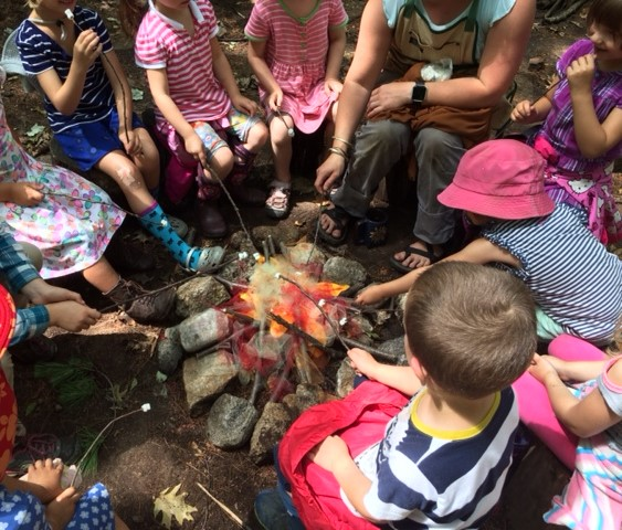 Buttercup Children with their pretend campfire made of stones and colored silks.