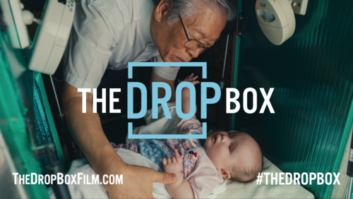Pastor Lee Jong-rak lifts a baby out of the drop box.