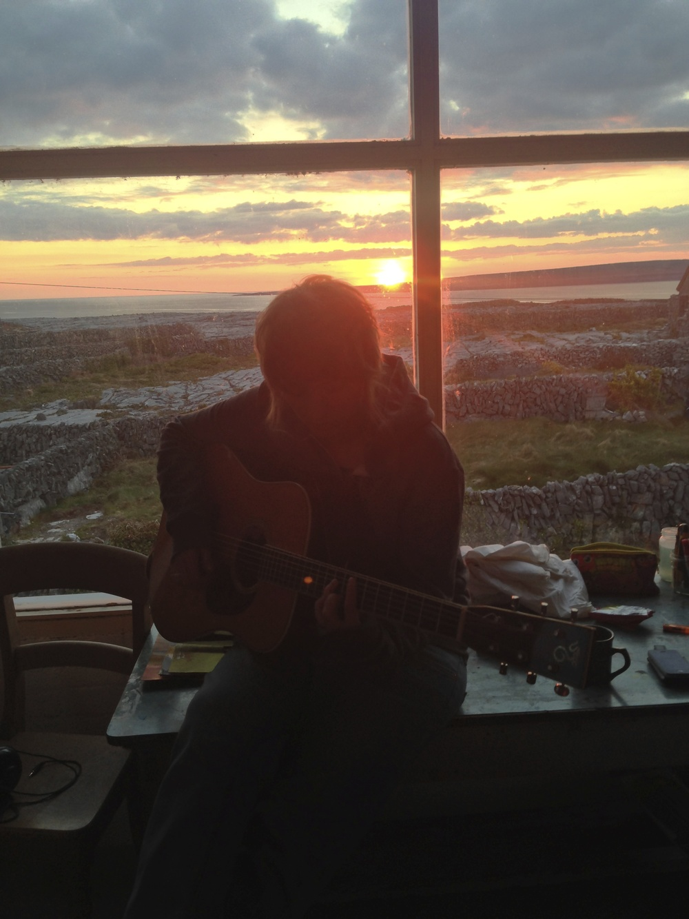 Klay playing guitar in front of the huge window with the sunset at her back.