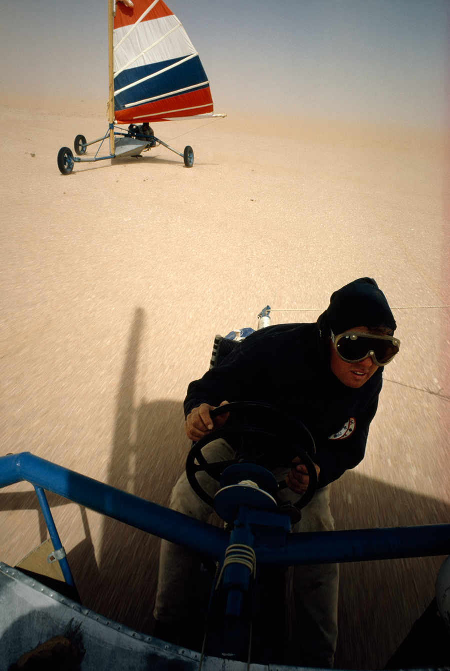 A land yacht pilot grips one wheel to steer and one to control sails in the Sahara Desert, Mauritania, November 1967.  PHOTOGRAPH BY JONATHAN BLAIR, NATIONAL GEOGRAPHIC