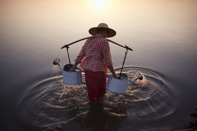 """A lady collects water in the river by a village in Bagan, Myanmar, 2013"" By Marcelo Salvador"