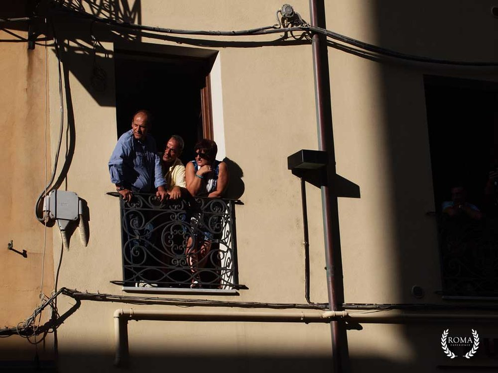People in Rome watching a parade outside the window
