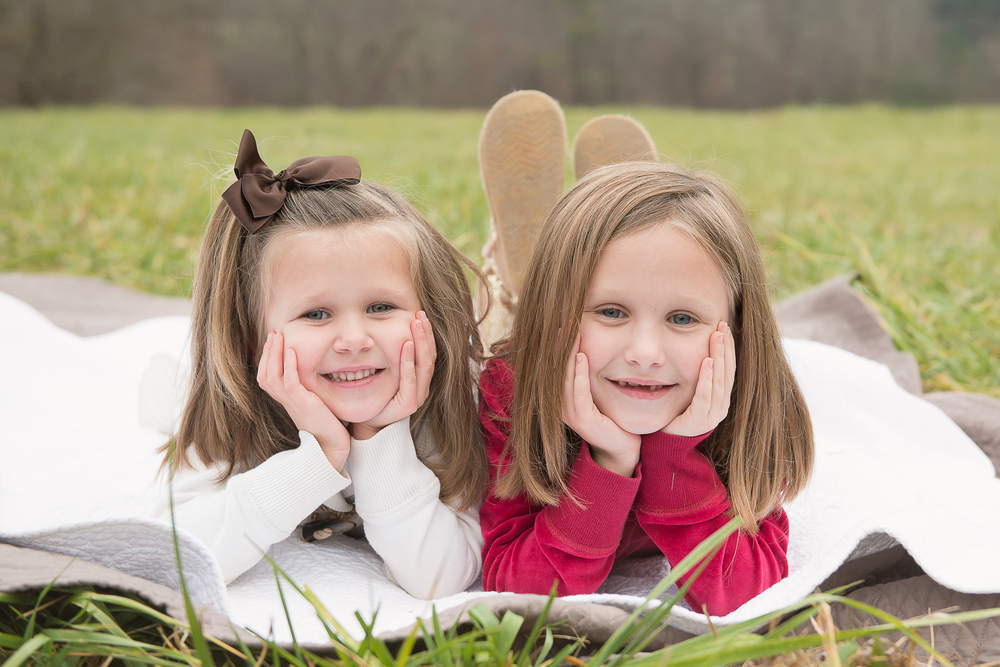 sisters on blanket posing and smiling
