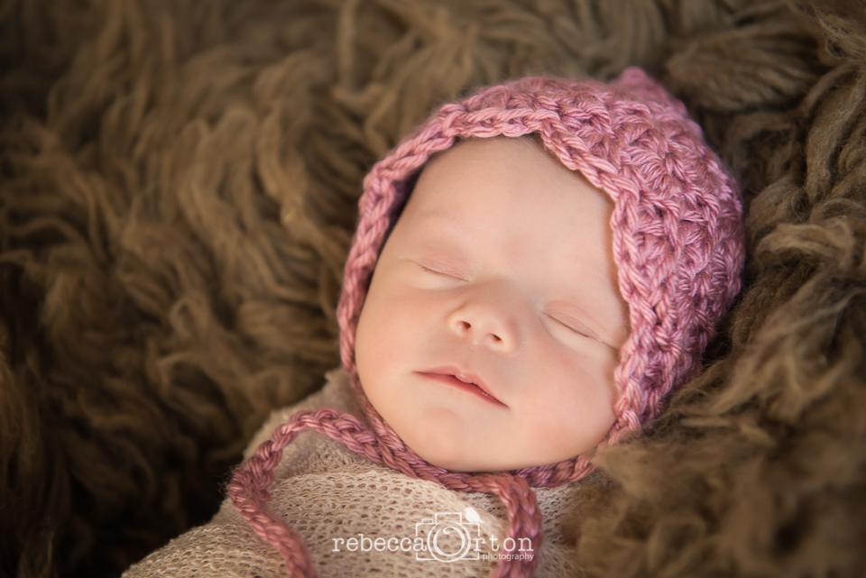sleepy baby girl in pink bonnet