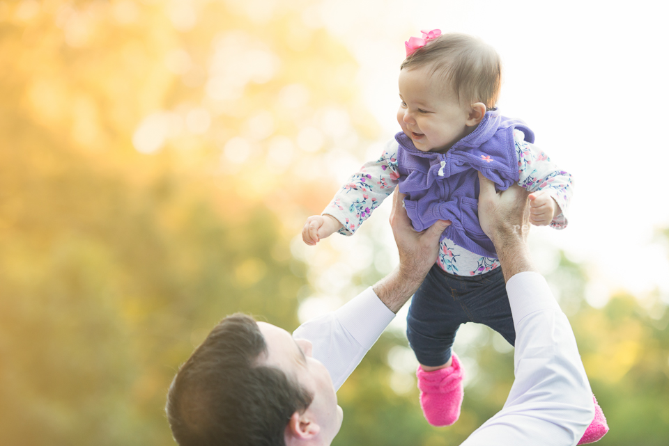 daddy lifting baby girl in air