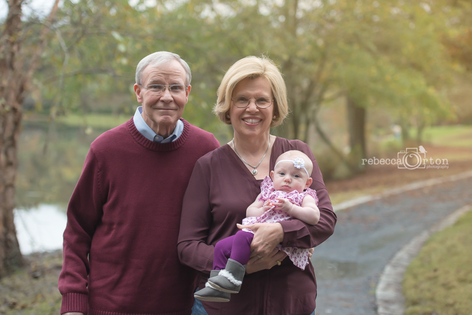 grandparents with 4 month old in purple