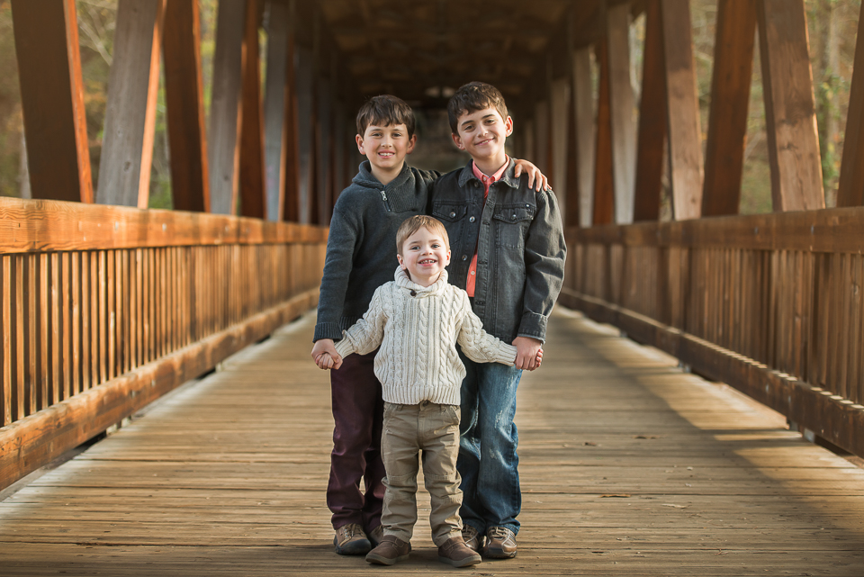 3 brothers smiling and holding hands