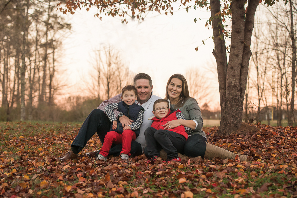 atlanta family sitting in fall leaves smiling