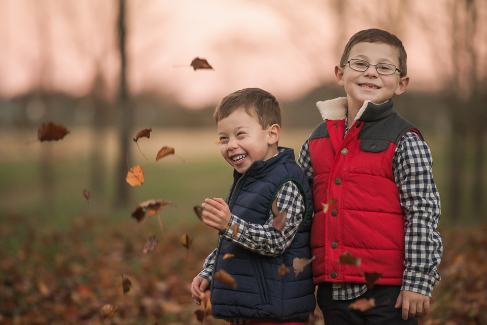 adorable young brothers playing in leaves