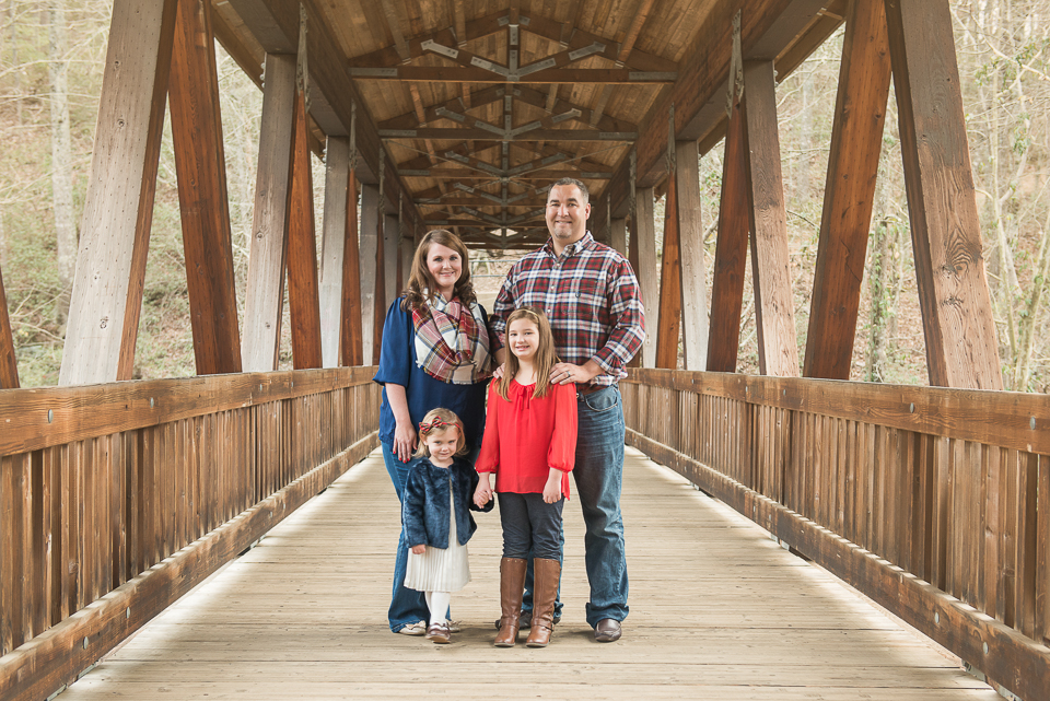 family of 4 posing and smiling on bridge