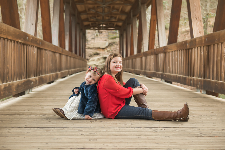 adorable sisters back to back on historic bridge