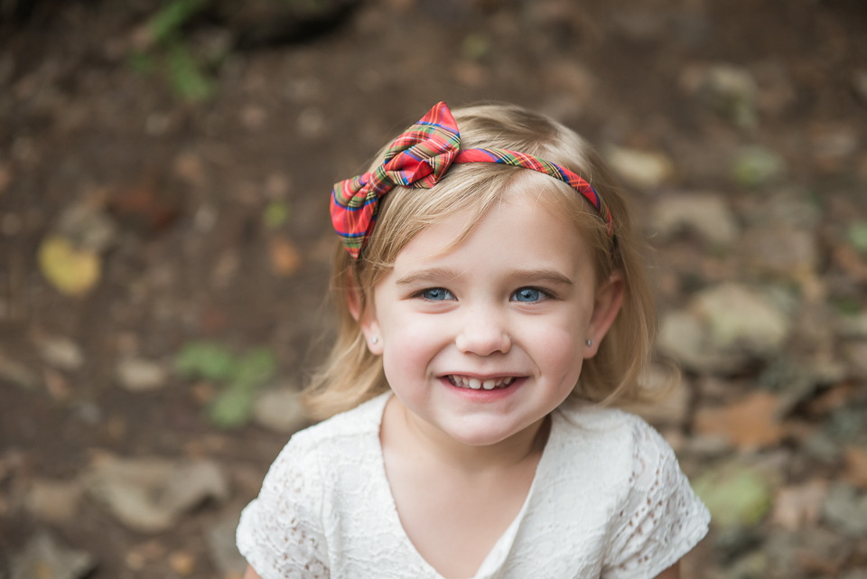 adorable blonde 2 year old smiling with red bow